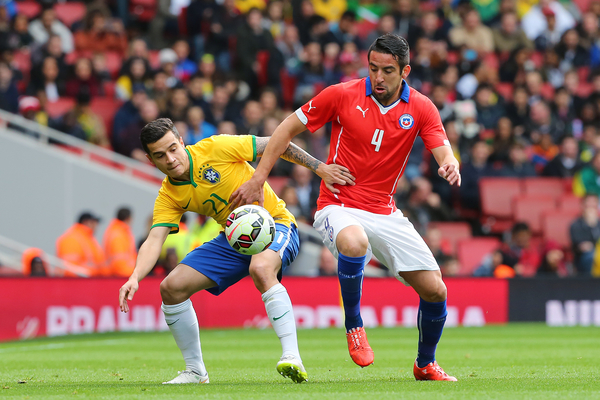 Philippe Coutinho of Brazil and Mauricio Isla of Chile battle for possession during the International Friendly match at the Emirates Stadium, London Picture by Richard Calver/Focus Images Ltd +44 7792 981244 28/03/2015