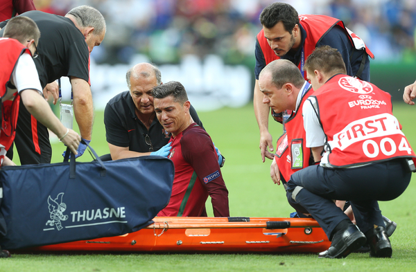 Cristiano Ronaldo of Portugal sits on the pitch injured as a stretcher is brought on during the UEFA Euro 2016 Final at Stade de France, Paris Picture by Paul Chesterton/Focus Images Ltd +44 7904 640267 10/07/2016