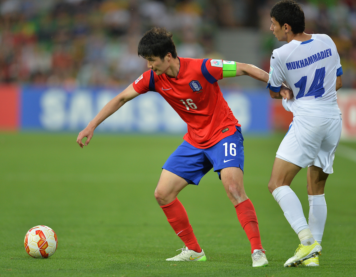 Ki Sung Yueng of Korea Republic (left) and Shukhart Mukhammadiev of Uzbekistan (right) contest for the ball during the AFC Asian Cup match between Korea Republic and Uzbekistan at Melbourne Rectangular Stadium (AAMI Park) Melbourne, Australia Picture by Frank Khamees/Focus Images Ltd +61 431 119 134 22/01/2015