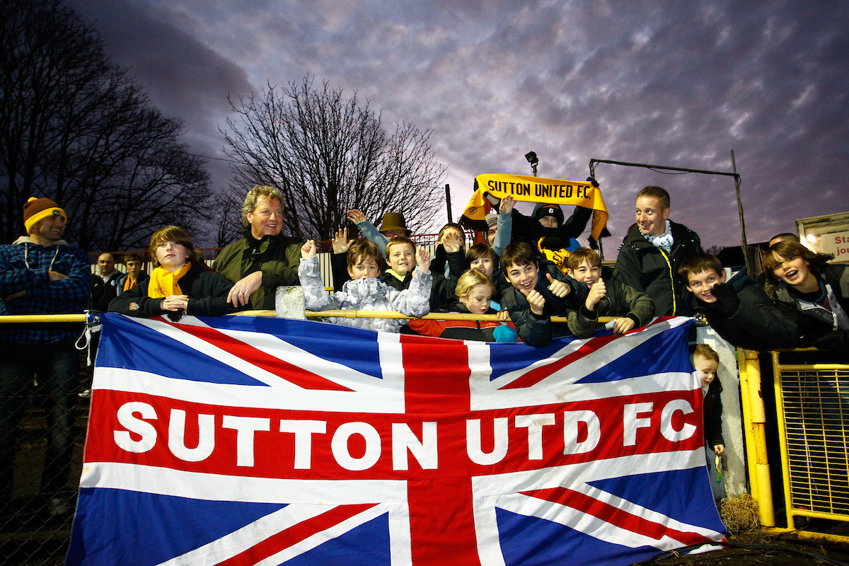Picture by Andrew Tobin/Focus Images Ltd. 07710 761829 . 4/12/11. Sutton United fans cheer their team on during the FA Cup 2nd round match between Sutton United and Notts County at The Borough Sports Ground, Surrey.