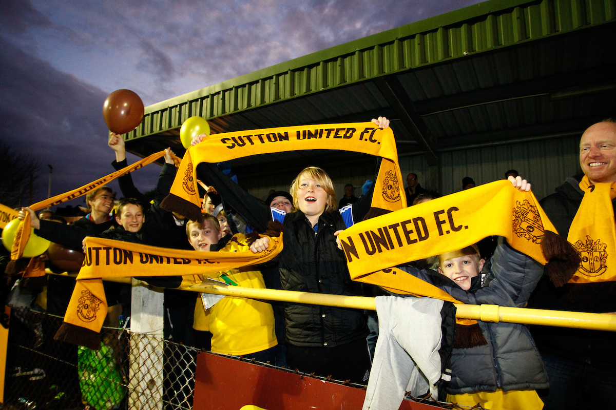 Picture by Andrew Tobin/Focus Images Ltd. 07710 761829.. 4/12/11.  Sutton United fans cheer their team on during the FA Cup 2nd round match between Sutton United and Notts County at The Borough Sports Ground, Surrey.