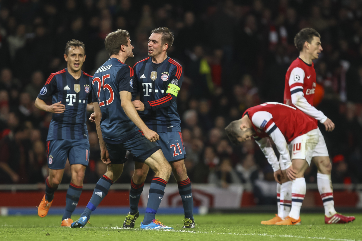 Thomas Müller of Bayern Munich celebrates with teammate Philipp Lahm of Bayern Munich after scoring his side's second goal during the UEFA Champions League match at the Emirates Stadium, London Picture by Daniel Chesterton/Focus Images Ltd +44 7966 018899 19/02/2014