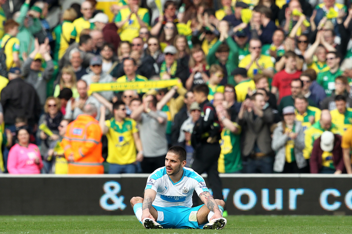 Aleksandar Mitrovic of Newcastle United looks dejected as the home fans celebrate victory at the end of the Barclays Premier League match at Carrow Road, Norwich Picture by Paul Chesterton/Focus Images Ltd +44 7904 640267 02/04/2016
