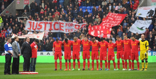 Picture by Seb Daly/Focus Images Ltd +447738 614630.13/04/2013.Liverpool fans hold banners relating to the Hillsborough disaster whilst players obverse a minutes silence during the Barclays Premier League match at the Madejski Stadium, Reading.